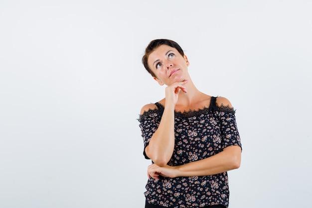 Donna matura appoggiando il mento sulla mano, tenendo la mano sotto il gomito, pensando a qualcosa in camicetta floreale, gonna nera e guardando pensieroso, vista frontale.