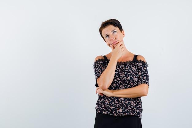 Donna matura appoggiando il mento a portata di mano, pensando a qualcosa in camicetta floreale e gonna nera e guardando pensieroso. vista frontale.