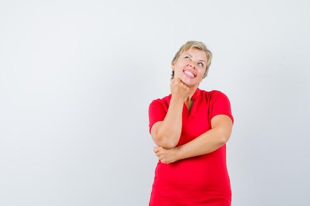 성숙한 여인 빨간 티셔츠에 올려 진 주먹에 턱을지지하고 희망을 찾고 있습니다.