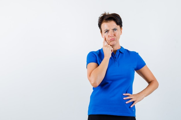 Mature woman pulling down her eyelid while thinking in blue t-shirt and looking sad , front view.