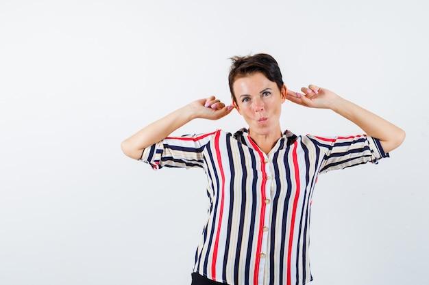 Зрелая женщина дергает за уши, кривые губы в полосатой блузке и выглядит удивленным. передний план.
