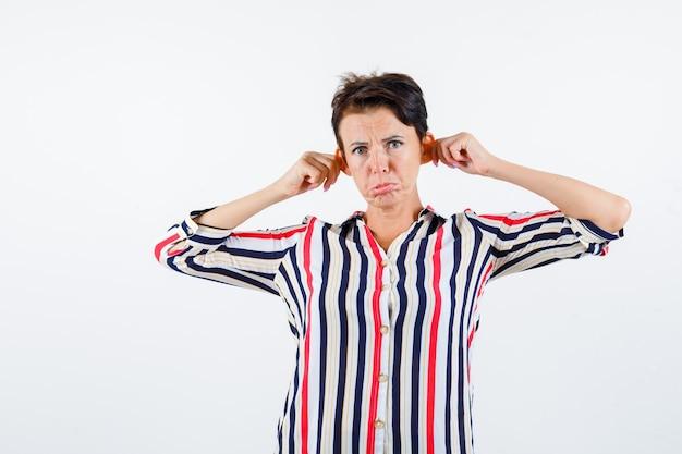 Зрелая женщина, потянув уши, изогнув губы в полосатой блузке и угрюмо глядя, вид спереди.