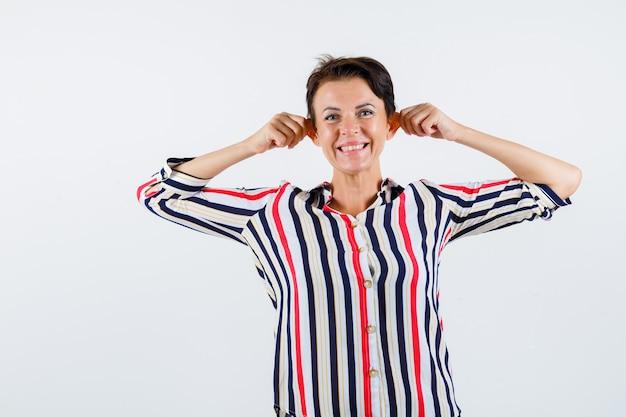 Зрелая женщина, потянув уши, улыбаясь в полосатой блузке и выглядя жизнерадостной, вид спереди.
