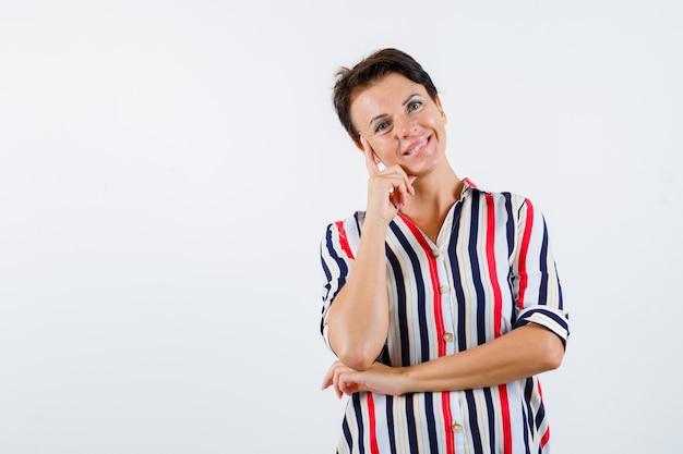 頬に人差し指を置き、ストライプのシャツを着て肘の下に片手を持ち、魅力的に見える成熟した女性。正面図。 無料写真