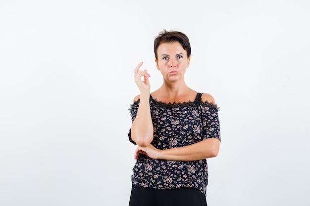 Donna matura alzando la mano, tenendo una mano sotto il gomito in camicetta floreale e gonna nera e guardando seria. vista frontale.