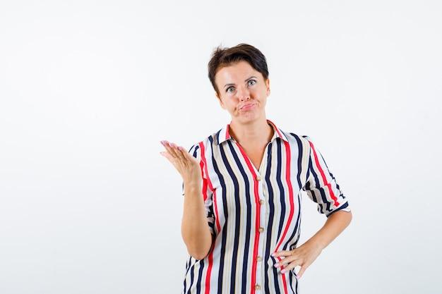 Зрелая женщина агрессивно поднимает руку в полосатой рубашке, вид спереди.