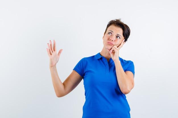 Donna matura alzando la mano mentre pensa in maglietta blu e guardando dubbioso, vista frontale.