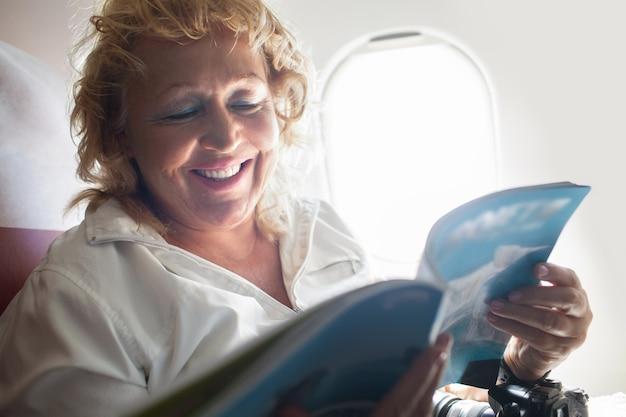 Mature woman reading magazine on a plane