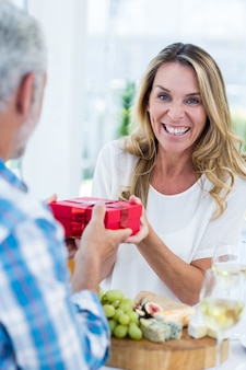 Mature woman receiving gift from husband