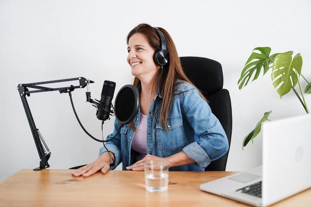 Mature woman recording a podcast inside studio