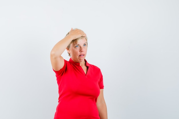Mature woman in red t-shirt holding hand on head and looking confused.
