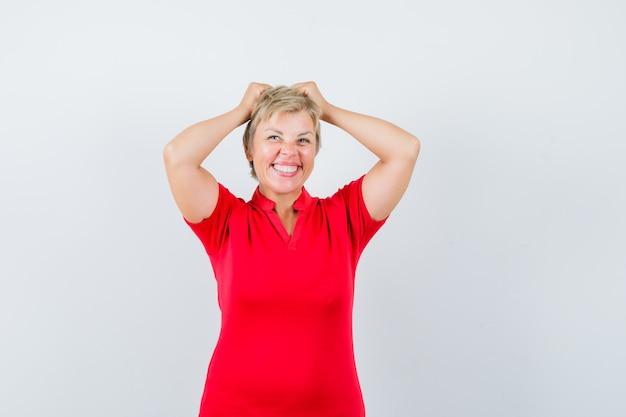 Donna matura in maglietta rossa che tiene le mani sulla testa e che sembra allegra.