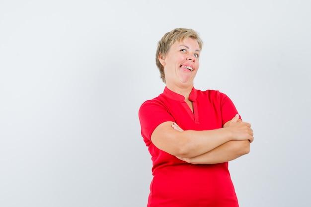 Donna matura in maglietta rossa in piedi con le braccia incrociate e guardando divertente