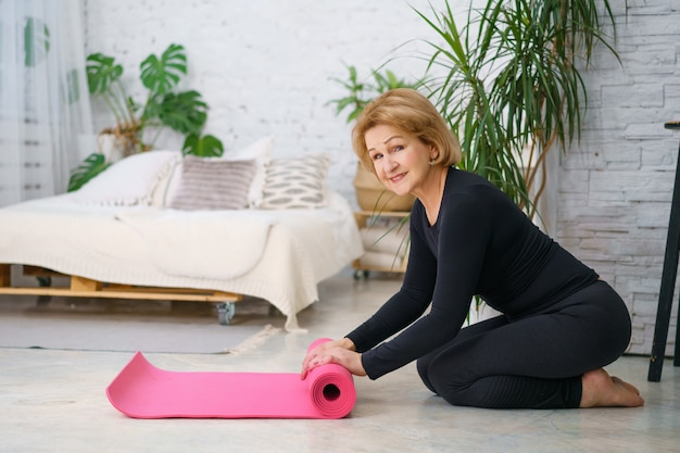Mature woman reeling off mat after training at home