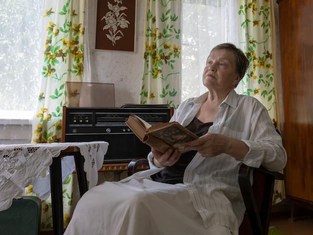 ミッドセンチュリーの家具とインテリアデザインの女性とリビングルームの肘掛け椅子で休んでいる成熟した女性...