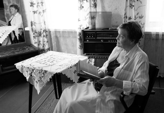 ミッドセンチュリーのインテリアデザインの女性の読書小説とリビングルームのアームチェアで休んでいる成熟した女性...