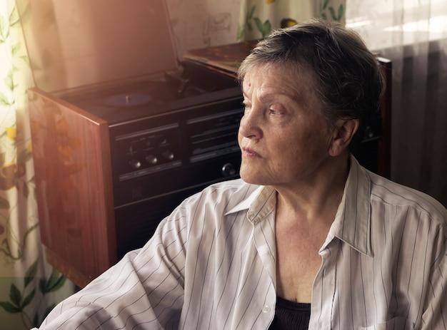 ターンテーブルで音楽を聴いているミッドセンチュリーのインテリアデザインのリビングルームで休んでいる成熟した女性...
