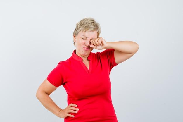 Зрелая женщина протирает глаз, плача в красной футболке и обиженно глядя.