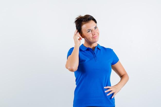 Зрелая женщина почесывает голову в голубой футболке и выглядит мечтательно, вид спереди.