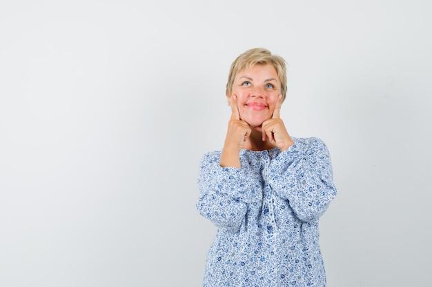 Donna matura in camicia mantenendo le dita sulle guance e guardando carino