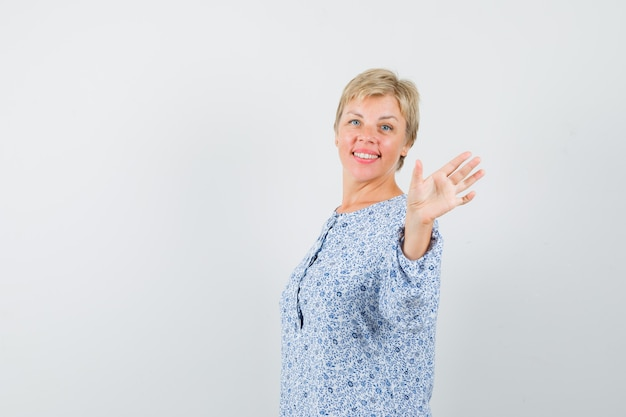 Mature woman in shirt waving hand to say goodbye and looking glad.