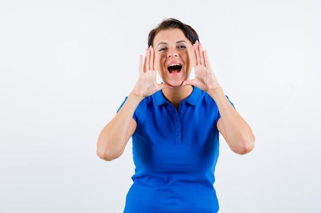 Зрелая женщина кричит или объявляет кого-то в синей футболке и выглядит взволнованной, вид спереди.