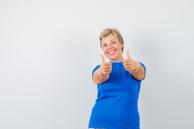 Donna matura che mostra i doppi pollici in su in maglietta blu e che sembra felice.