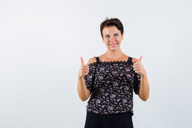 花柄のブラウスと黒いスカートで二重の親指を見せて、陽気に見える成熟した女性、正面図。
