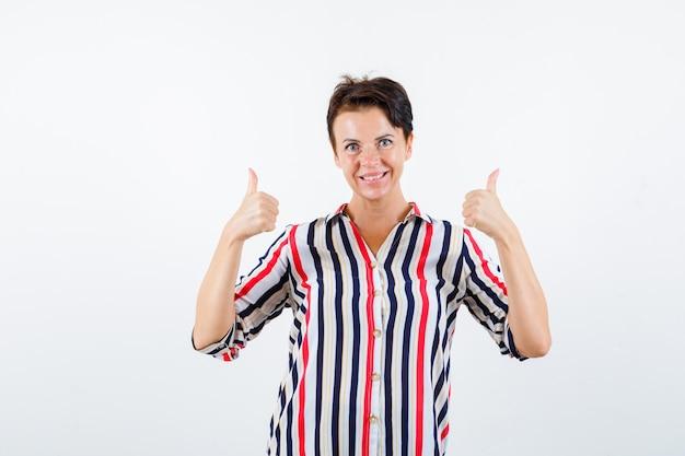ストライプのシャツを着て二重の親指を見せて幸せそうに見える成熟した女性。正面図。