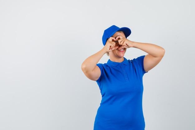 青いtシャツでハートのジェスチャーを示して嬉しそうに見える成熟した女性。