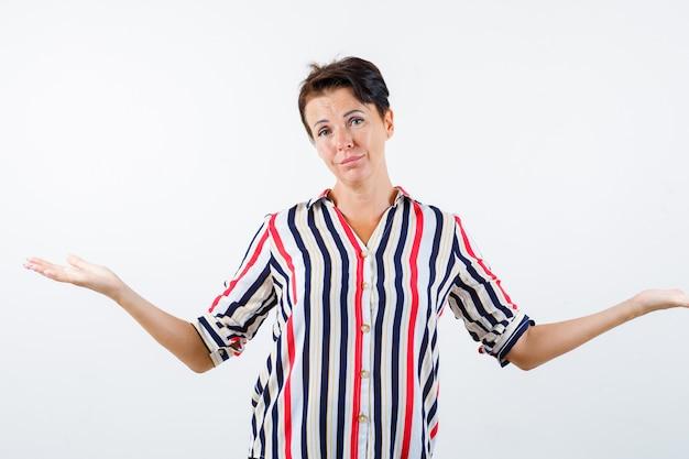 縞模様のシャツで無力なジェスチャーを示し、困惑しているように見える成熟した女性、正面図。