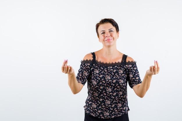 Зрелая женщина показывает жест денег в цветочной блузке и черной юбке и выглядит жизнерадостной, вид спереди.