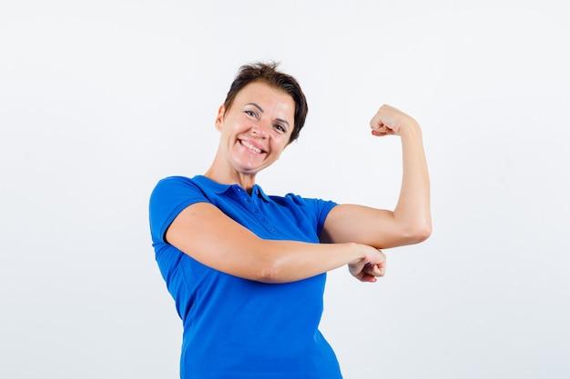 青いtシャツで腕の筋肉を見せて嬉しそうに見える成熟した女性。正面図。