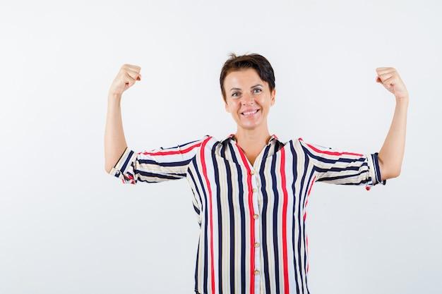 Donna matura che mostra i muscoli in camicia a righe e guardando fiducioso, vista frontale.