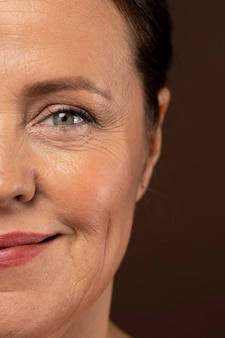 Зрелая женщина демонстрирует половину своего лица с макияжем