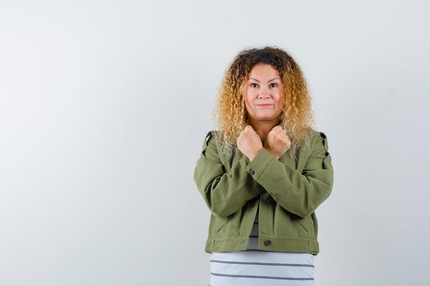 Donna matura che mostra gesto di protesta in giacca verde, t-shirt e guardando fiducioso, vista frontale.
