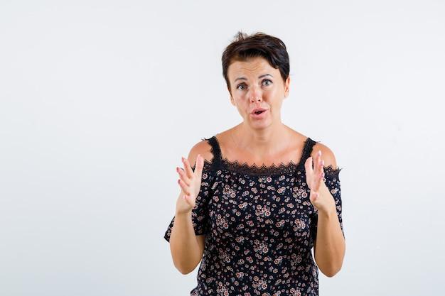 Donna matura che mostra le scale in camicetta floreale, gonna nera e sembra eccitata. vista frontale.