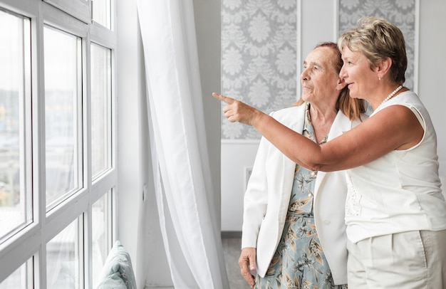 Mature woman showing something to her mother from window