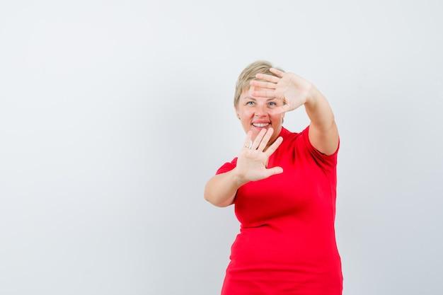 赤いtシャツで停止ジェスチャーを示し、恥ずかしそうに見える成熟した女性。