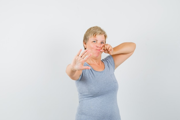 Mature woman showing stop gesture with mouth shut as zip in grey t-shirt and looking scared