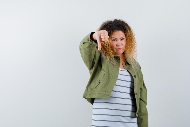 緑のジャケット、tシャツで親指を下に見せて、不機嫌そうに見える成熟した女性、正面図。