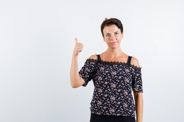 花柄のブラウス、黒いスカートに親指を立てて自信を持って見える成熟した女性。正面図。