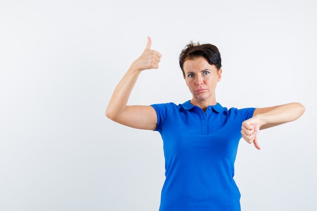 Mature woman showing thumbs up and down in blue t-shirt and looking hesitant , front view.