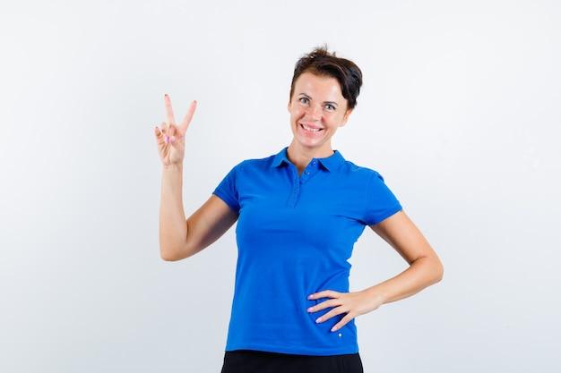 Donna matura che mostra il gesto di vittoria in maglietta blu e che sembra sicura. vista frontale.