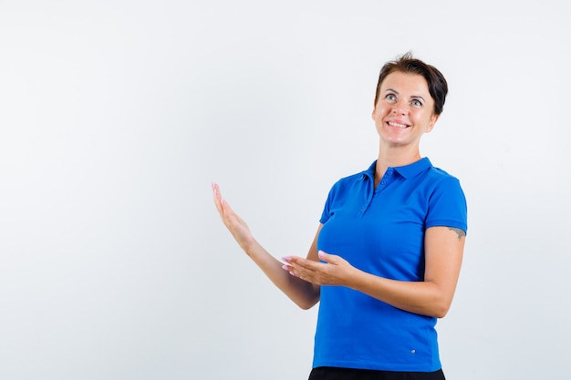 青いtシャツで歓迎のジェスチャーを示し、幸せそうに見える成熟した女性、正面図。