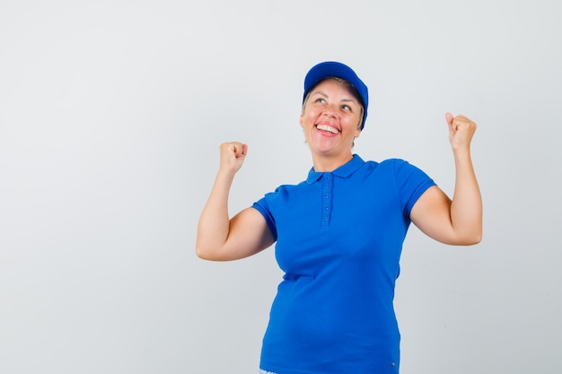 Mature woman showing winner gesture in blue t-shirt and looking lucky.