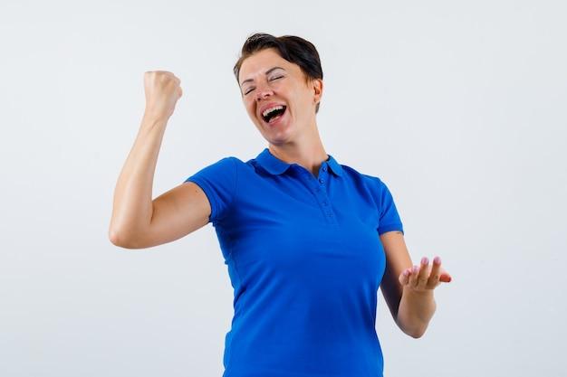 파란색 티셔츠에 우승자 제스처를 보여주는 성숙한 여자와 행복을 찾고. 전면보기.
