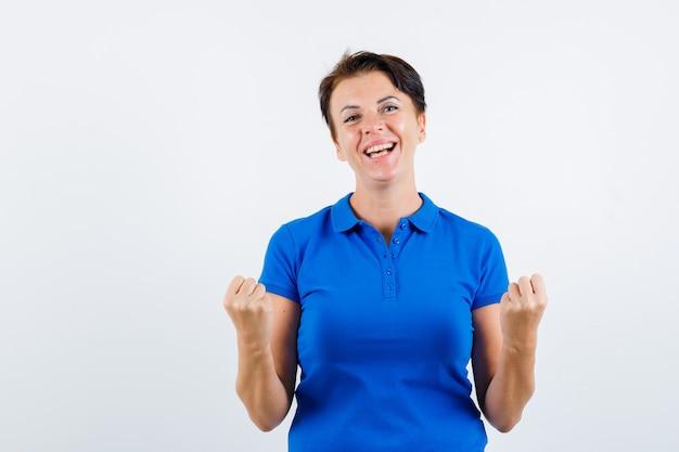 파란색 티셔츠에 승자 제스처를 표시하고 운이 좋은 찾고 성숙한 여자. 전면보기.