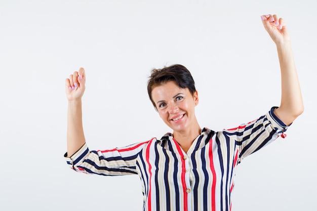 ストライプのシャツで勝者のジェスチャーを示し、幸せそうに見える成熟した女性、正面図。
