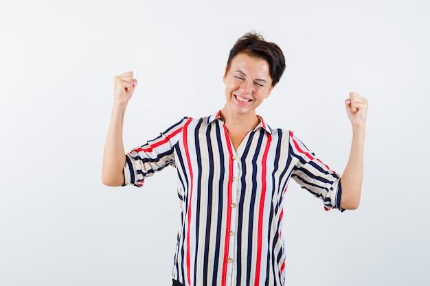 스트라이프 셔츠에 우승자 제스처를 보여주는 성숙한 여인 운이 좋은 찾고. 전면보기.